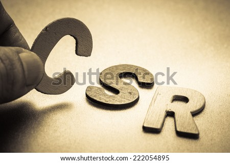 Closeup finger picking a small English letter to put in the CSR (Corporate social responsibility)  abbreviation - stock photo