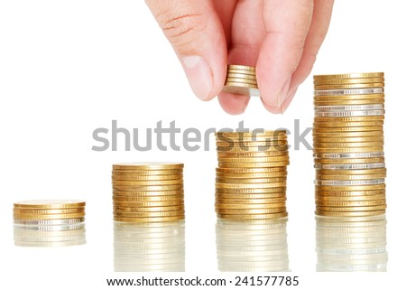 closeup finger put coins to coin stack,saving concept on white background