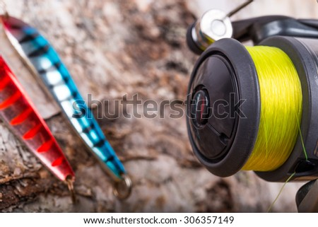 closeup fishing bait lures and reel with line on wooden background - stock photo