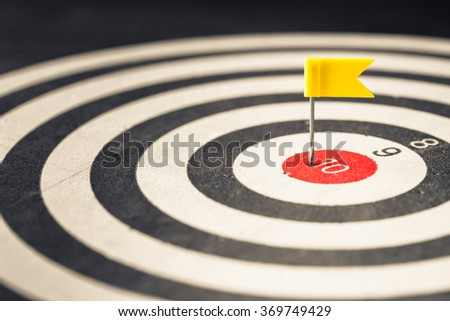 Closeup flag push pin in the center of dartboard - stock photo