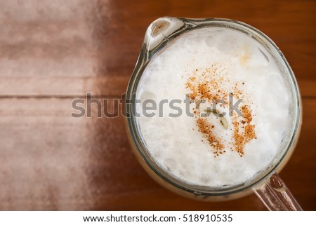 Closeup foam with cinnamon topping of Ice cappuccino in a glass of jar. Top view. In cafe. Favorite menu of drinks. Refreshment drink.
