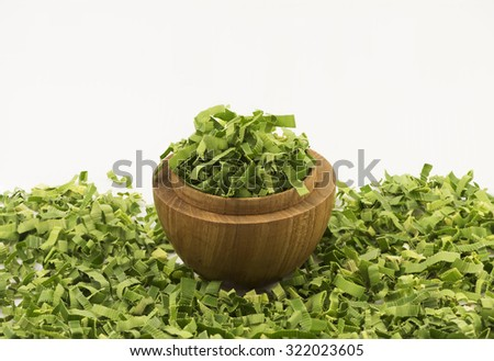 Closeup focus on shredded pandan leaf in a wooden bowl. Partially focus loose leaf at foreground and white background for text. The sweet fragrance herbal tea leaf is value for its medicinal benefits. - stock photo