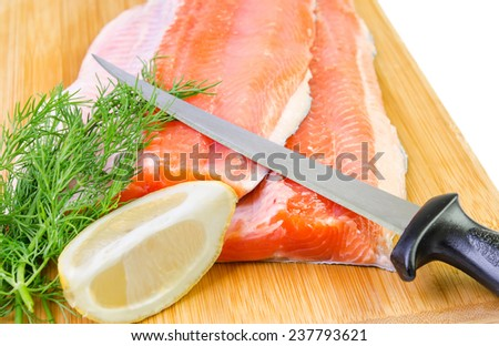 Closeup for trout fish fillet with knife on a kitchen board - stock photo