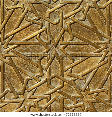Closeup fragment of an old door, decorated by bronze geometrical ornament in retro east style. Useful for background. - stock photo