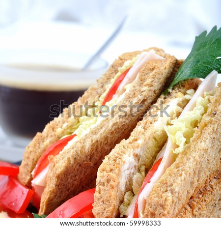 closeup fresh and delicious classic club sandwich over a black glass dish with coffee and vegetable - stock photo