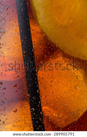 closeup from a cola glass with dew drops, lemon and straw - stock photo