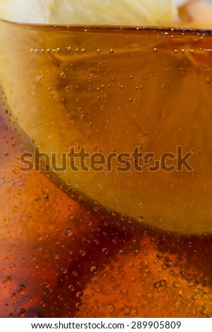 closeup from a cola glass with lemon and ice cubes - stock photo