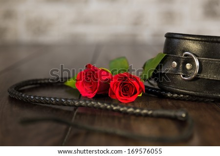 closeup from bdsm toys and a red rose - stock photo