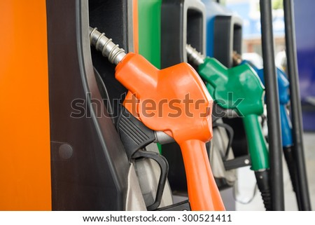 Closeup fueling fuel nozzle car in gas station - stock photo