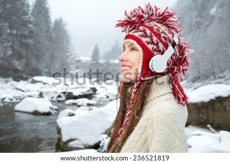 Closeup funny winter girl listening to music over snowy landscape - stock photo