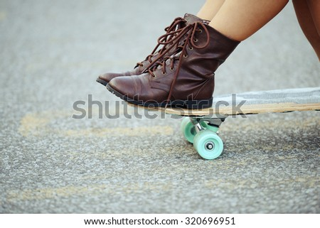 closeup girl with boots sitting on skate board - stock photo