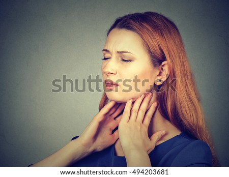 Closeup girl with sore throat touching her neck. Sick young woman having pain in her throat isolated on gray wall background