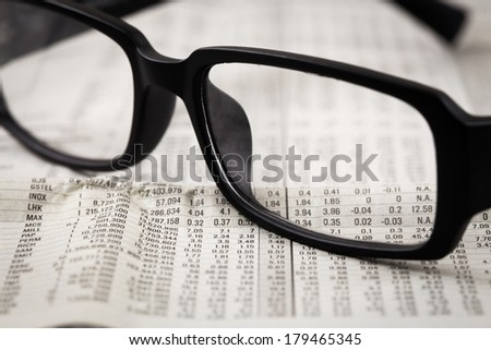 closeup glasses on financial newspaper. Accounting
