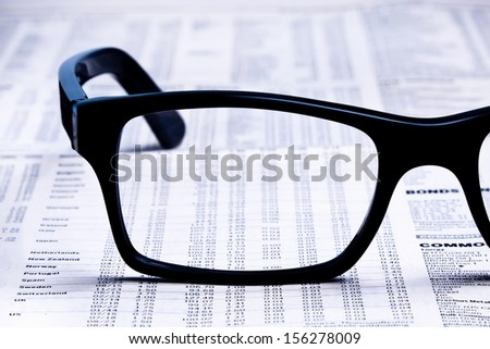 closeup glasses on financial newspaper under light tint blue  - stock photo