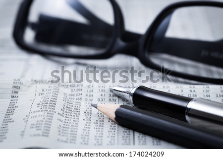 closeup glasses on financial newspaper with pen - stock photo