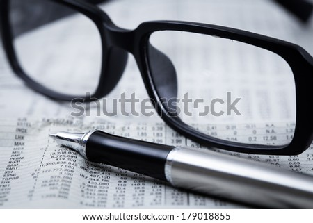 closeup glasses on financial newspaper with pen