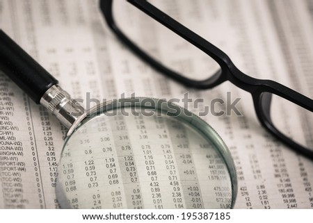 closeup glasses on financial newspaper with pen.Accounting