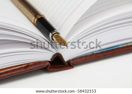 Closeup Golden Fountain Pen on Notebook - stock photo