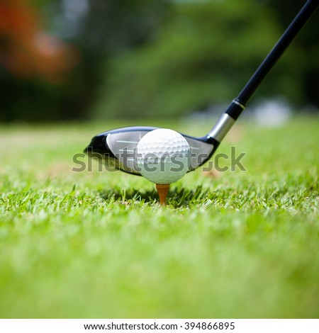 Closeup golf ball on tee in front of driver - stock photo