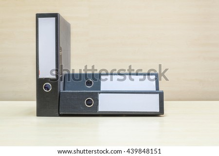 Closeup group of document file on blurred wooden desk and wall textured background in the meeting room under window light - stock photo