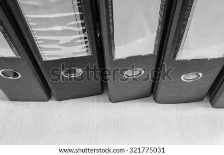 Closeup group of document file on wood desk background in black and white tone - stock photo