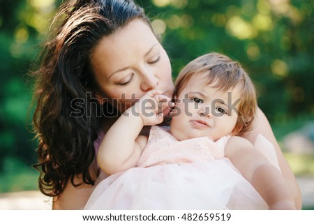 Closeup group portrait of beautiful white Caucasian brunette mother holding hugging daughter kissing her in cheek on sunny spring summer day in park outside