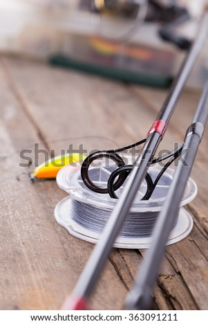 closeup guide rings on graphite rods and watted cord with blur background from fishing tackles and lure boxes. - stock photo