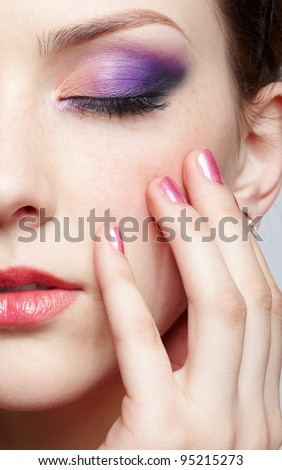 closeup half-face portrait of young beautiful woman with eyes closing eyes and touching face with manicured fingers - stock photo