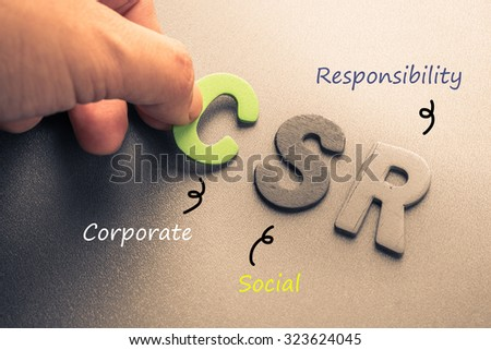 Closeup hand arrange wood letters as CSR abbreviation(Corporate social responsibility) - stock photo