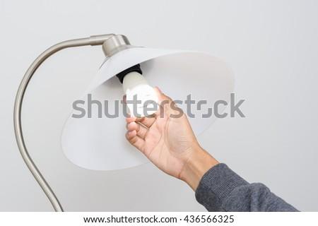 closeup hand changing an electric light bulb - stock photo