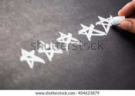 Closeup hand drawing five stars rating on chalkboard - stock photo