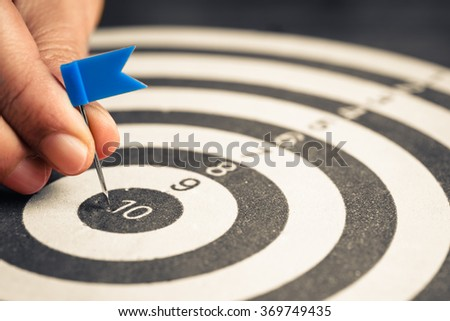 Closeup hand going to put a flag push pin into the center of dartboard - stock photo