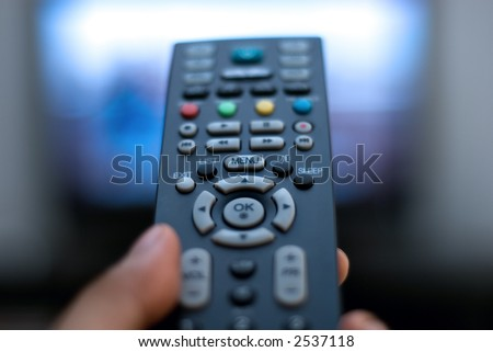 Closeup hand holding a TV remote control against the television - stock photo