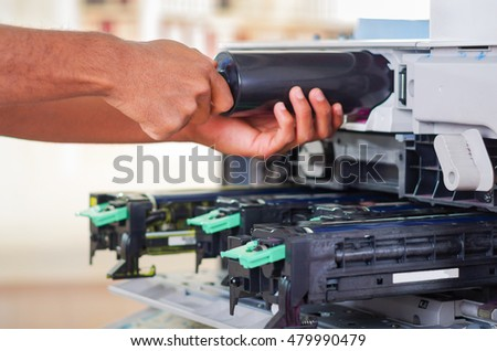 Closeup hand in front of open photocopier during maintenance repairs using handheld tool, black mechanical parts