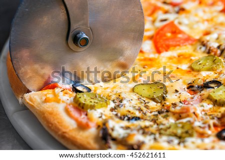 Closeup hand of chef baker in white uniform cutting pizza at kitchen - stock photo