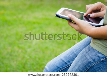 Closeup hand of woman in casual clothes using tablet outdoor in the park