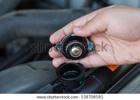 Closeup hand open valve metal cover on an radiator for engine cooling - stock photo