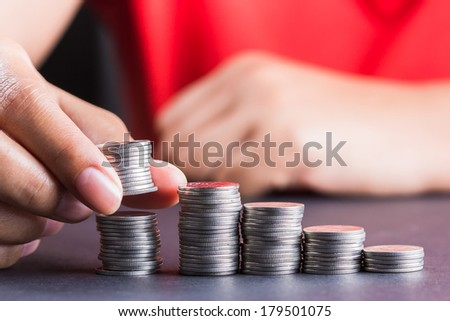 Closeup hand putting a coins heap into the row - stock photo
