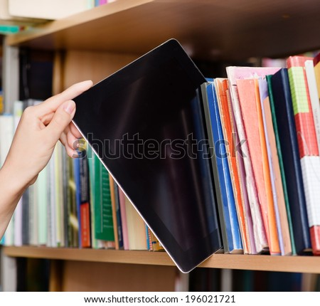 closeup hand putting a tablet pc in the shelves in the library - stock photo