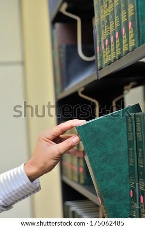 closeup hand selecting book from a bookshelf  - stock photo