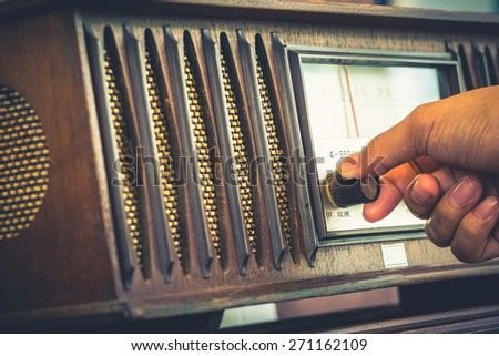Closeup hand turn on the old radio to listen, retro color style - stock photo