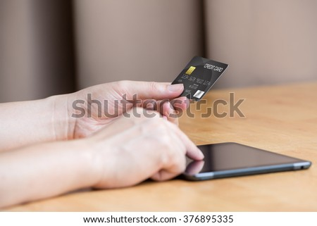 closeup hand using tablet and credit card shopping online