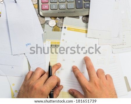 Closeup hand working  with receipts and calendar page - stock photo