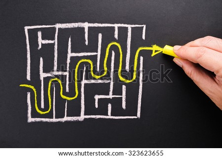 Closeup hand writing way out of maze game on chalkboard