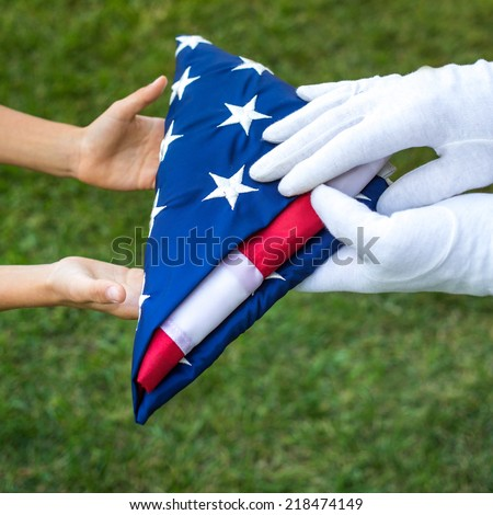 Closeup hands hold american flag carefully folded over green background. concept,  daylight outdoor shot - stock photo