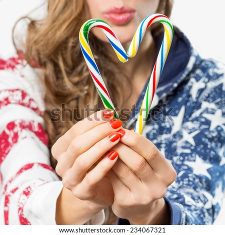 Closeup hands hold candy canes forming heart - stock photo