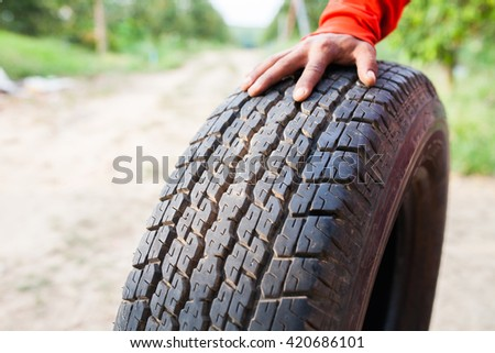 closeup hands holding a tire or tyre on the road - stock photo
