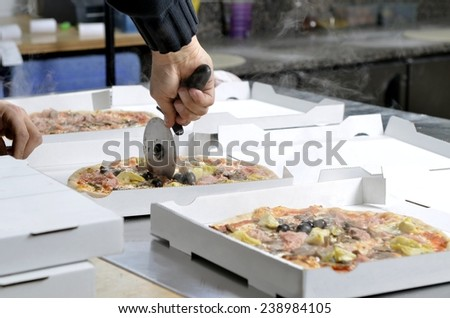 Closeup hands of chef pizza man cutting pizzas at kitchen with cutter for take away - stock photo