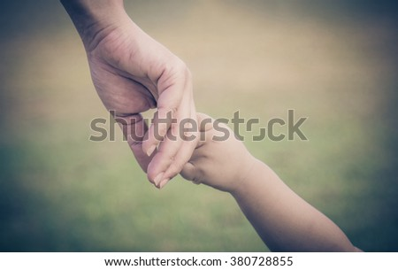 Closeup hands of mother and child background. Concept of love care newborn  and family. Baby hand holding mother in spring day outdoors. Adult help and kids dark tone. - stock photo