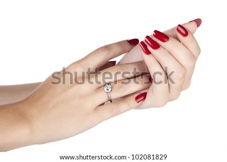 closeup hands of young woman with red manicure polished nails wearing an expensive engagement ring with a diamond - stock photo